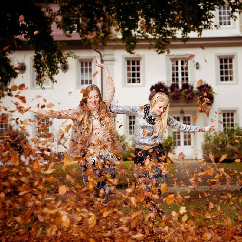 Modefotografie in herbstlichen Blätter im Schlosspark